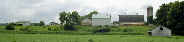 view from a field of row of farm buildings atop a bluff